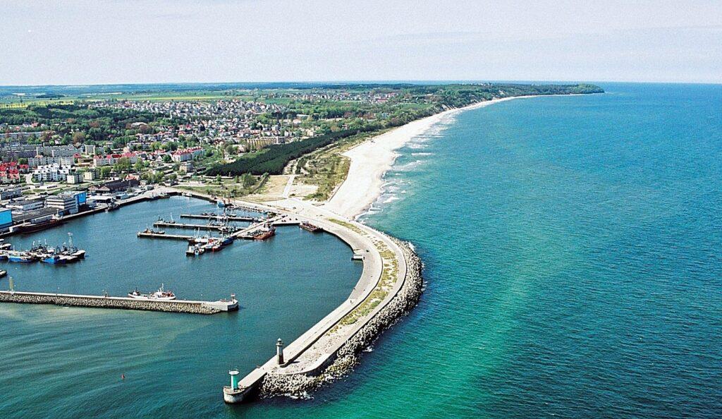 Zdjęcie z lotu ptaka, ukazujące falochron osłonowy portu we Władysławowie na tle panoramy wybrzeża w kierunku północno-zachodnim.