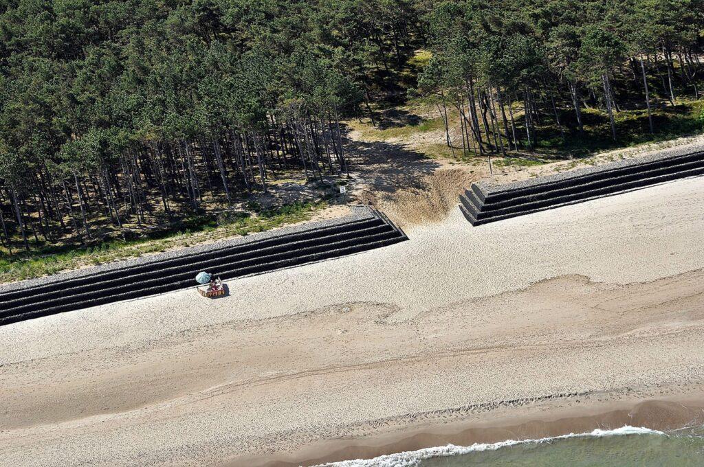 Zdjęcie z lotu ptaka przedstawiające opaskę z koszy gabionowych, zbudowaną pomiędzy plażą a lasem.