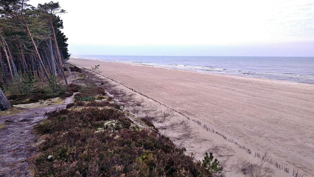 Zdjęcie szerokiej, sztucznie utworzonej w wyniku refulacji, plaży, pod którą znalazło się umocnienie w postaci opaski gabionowej.
