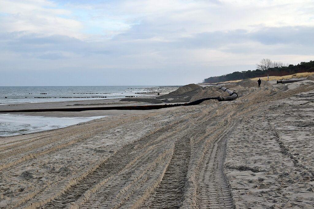 Zdjęcie z plaży, na której trwa refulacja. Widoczne hałdy piachu, gruba rura, którą dostarczany jest piasek z dna morskiego oraz rzędy drewnianych pali, tworzących ostrogi.