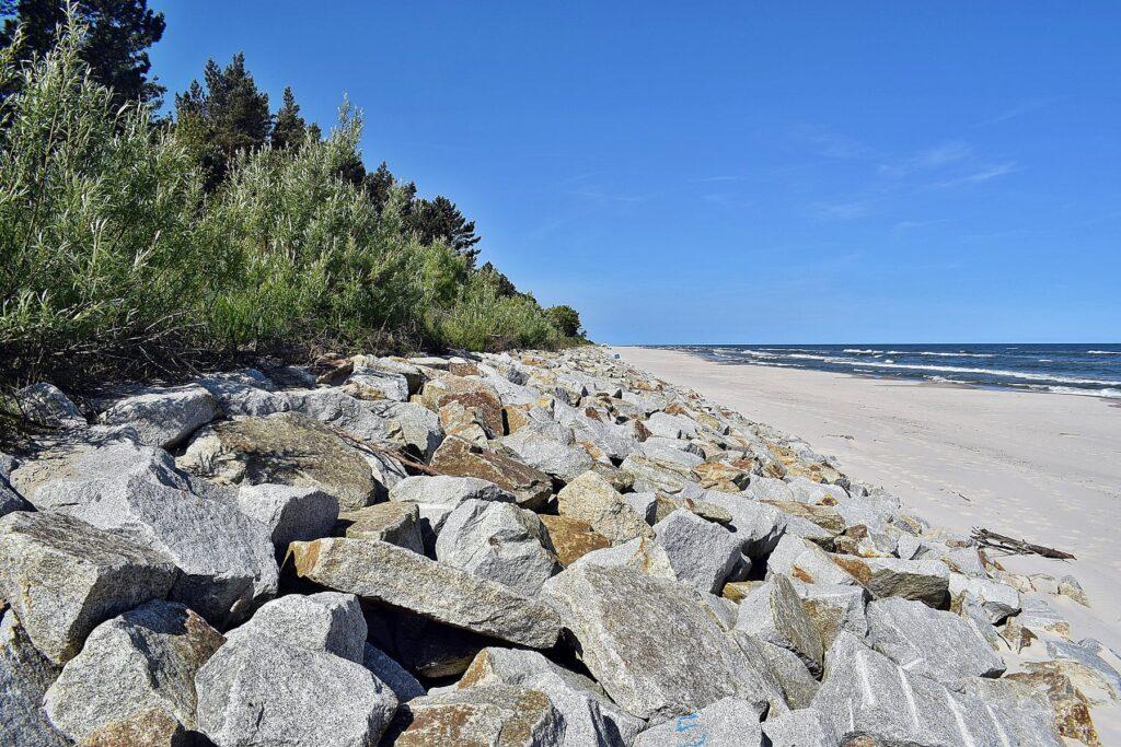 Zdjęcie umocnionego narzutem kamiennym wału wydmowego, na którego koronie widoczna jest bujna roślinność.