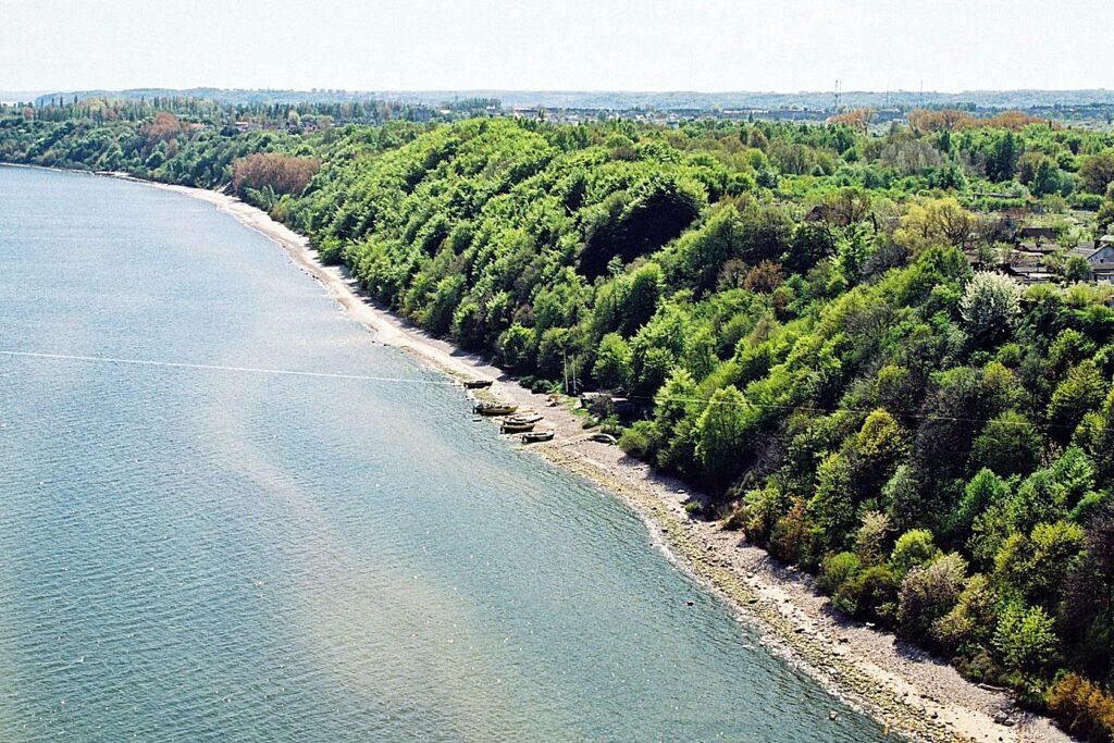 Zdjęcie z lotu ptaka ukazujące zbocze klifowe gęsto porośnięte roślinnością wysoką, wąską kamienistą plażę oraz przystań rybacką.