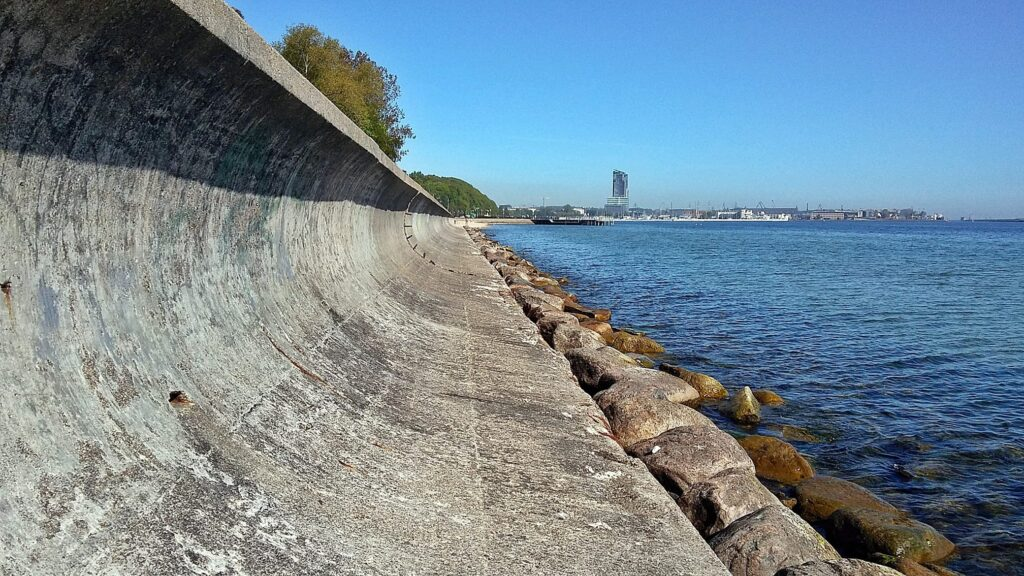 Zdjęcie umocnienia brzegowego w postaci betonowej opaski brzegowej z odbijaczem fal posadowionej na palach, zrobione od strony morza w kierunku północnym.