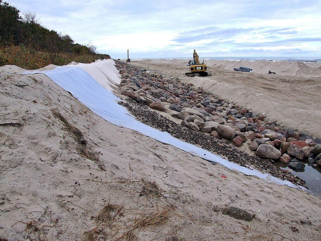 Zdjęcie etapu wbudowywania narzutu kamiennego w naturalny wał wydmowy. Widoczne są geowłókniny, frakcje kamieni o różnej wielkości oraz sprzęt budowlany.
