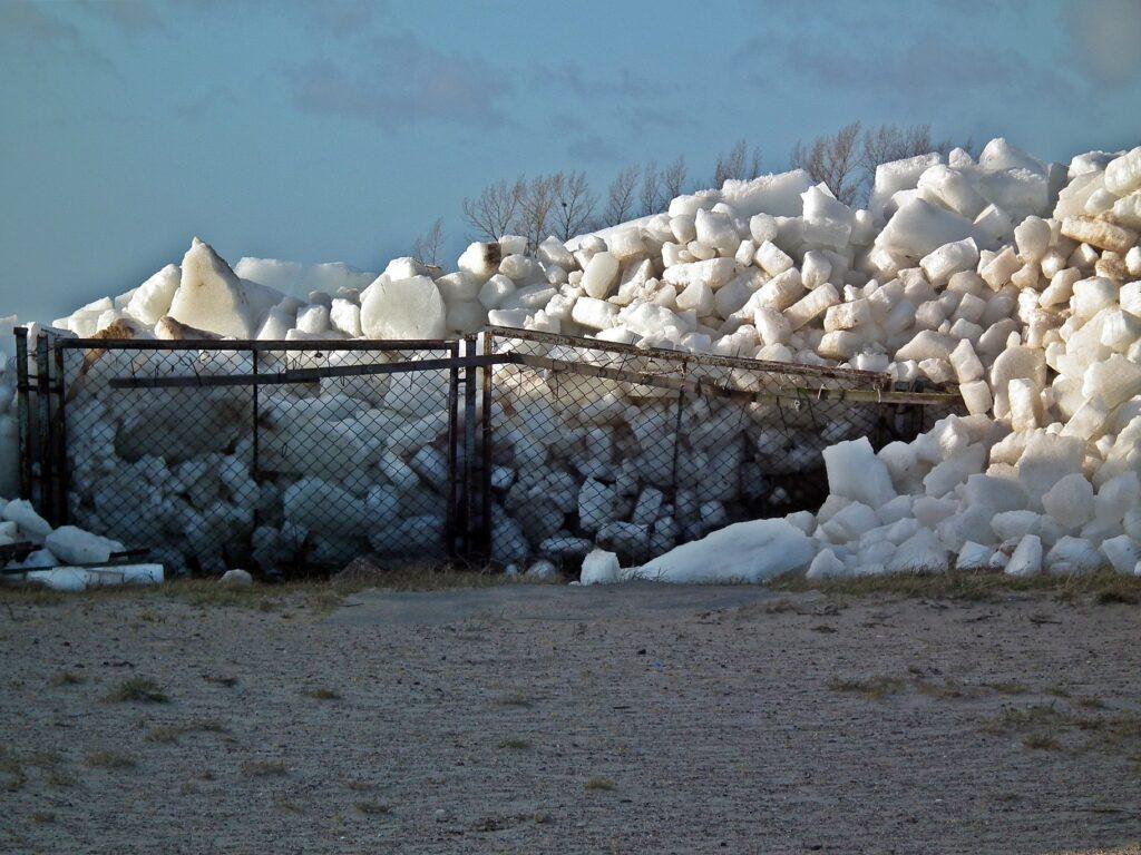 Zdjęcie przedstawiające ogromną ilość kry lodowej, wepchniętej przez fale na ląd w Chałupach. Widoczna góra lodu oraz zniszczone ogrodzenie.