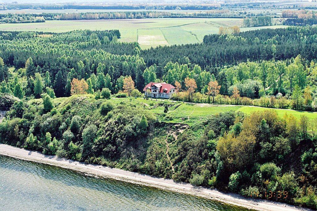 Zdjęcie z lotu ptaka obrazujące domek w odległości kilkudziesięciu metrów od krawędzi zbocza, na którym widoczne jest wydeptane zejście.