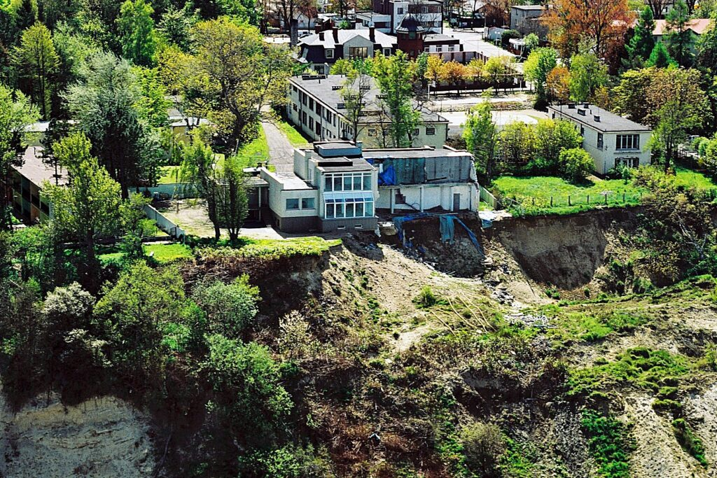 Zdjęcie z lotu ptaka ukazujące budynek mieszkalny uszkodzony na skutek osuwiska.