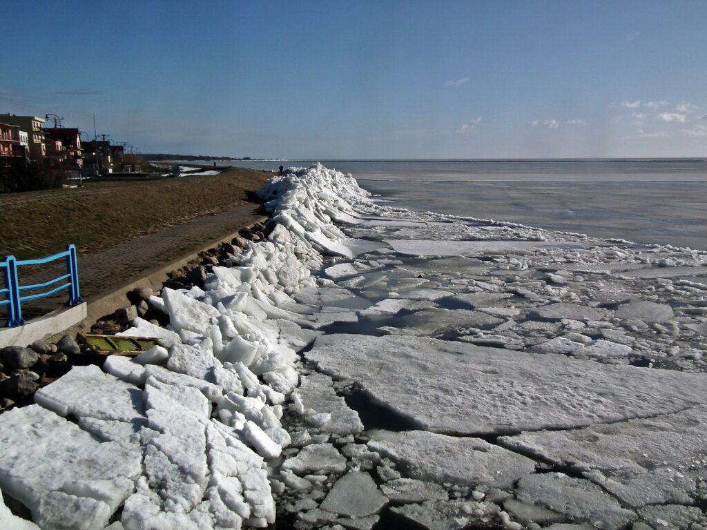 Zdjęcie brzegu Zatoki Puckiej w Kuźnicy, na który wpychane są kry lodowe