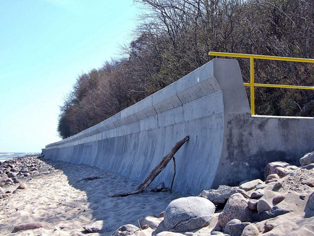 Zdjęcie betonowej opaski brzegowej z odbijaczem fal, zrobione z poziomu plaży.